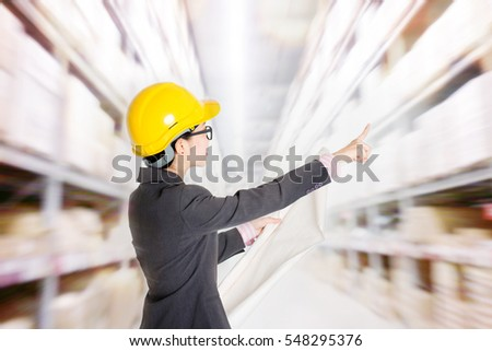 Young Asian female store manager with hard hat counting stock at warehouse. Shelves with goods at background.