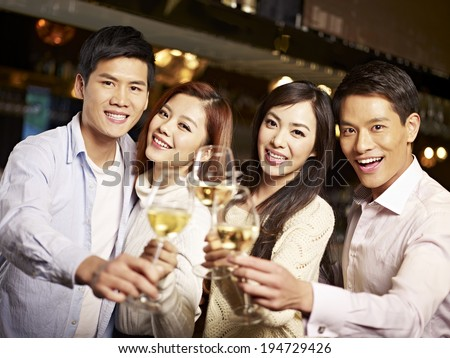 young asian friends couples enjoying party in pub.