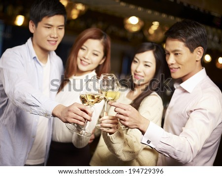 young asian friends couples enjoying party in pub, focus on hands and glasses.