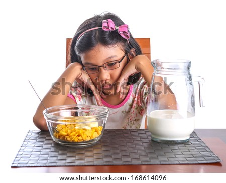 Young Asian girl bored looking face looking at her breakfast of cereal and milk. - stock photo