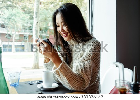 Young Asian Girl drinking coffee / tea and using digital smart-phone in a coffee shop - stock photo
