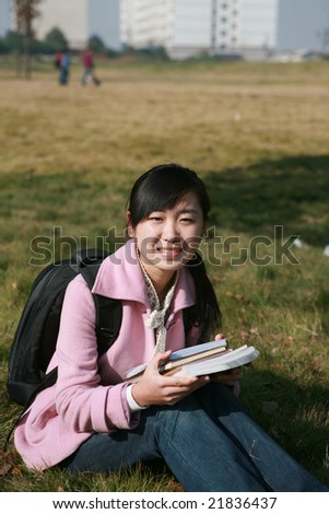 young asian girl holding books in college