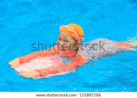 young asian girl playing in the swimming pool - stock photo