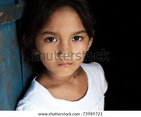 Young Asian girl portrait - child from Philippines against blue door and black background. - stock photo