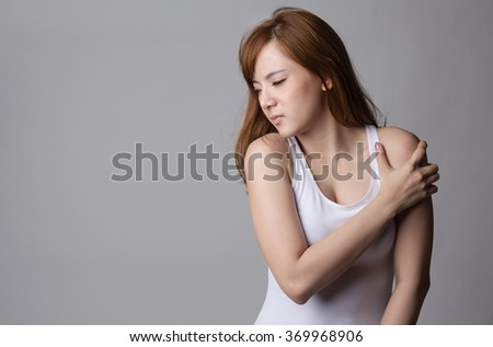 Young asian girl with shoulder pain - stock photo