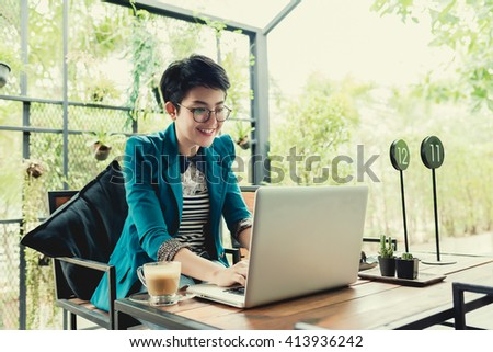 young Asian girl working on laptop in cafe. using laptop in home. using laptop in coffee shop - stock photo
