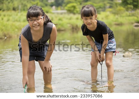 Young Asian girls catching fishes in river