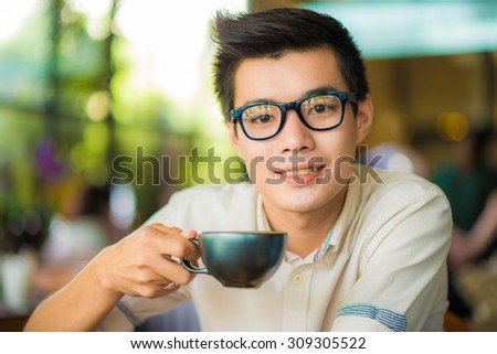 Young asian guy drinking coffee while computing at a student cafe  - stock photo