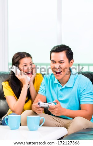 Young Asian handsome couple having leisure time together and playing with laptop video game console and phone on couch