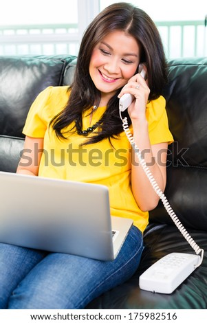 Young Asian handsome woman sitting on couch multitasking by using laptop and telephoning with phone - stock photo