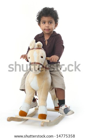Young Asian Indian boy riding on a felt rocking horse
