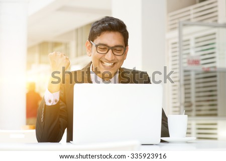 Young Asian Indian business people celebrating success, using a laptop at cafe, with a cup of coffee. India male business man, modern building with beautiful golden sunlight as background. - stock photo