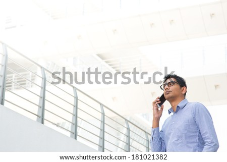 Young Asian Indian businessman on the phone, male business man, real modern office building as background. - stock photo