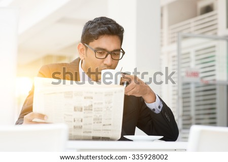 Young Asian Indian businessman sipping coffee and reading newspaper at cafe. India male business man, modern office building with beautiful golden sunlight as background. - stock photo