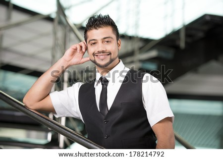 Young Asian Indian businessman standing on office background - stock photo