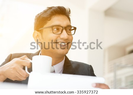 Young Asian Indian businessman using tablet pc at cafe, relaxing with a cup of coffee. India male business man, modern office building with sunlight as background. - stock photo