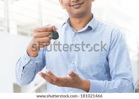 Young Asian Indian estate agent or salesman holding a key, India male business man, real modern office building as background. - stock photo