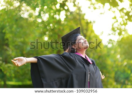 Young Asian Indian female student open arms outdoor on graduation day - stock photo