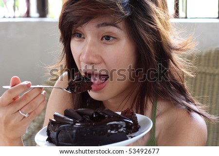 young asian lady enjoying a piece of cake - stock photo