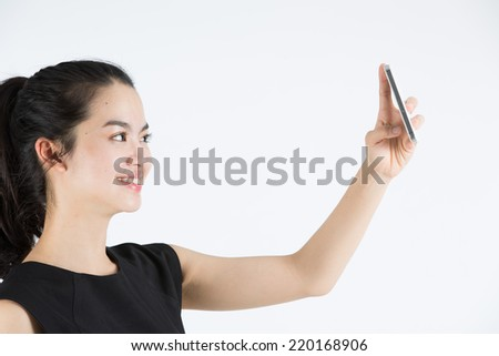 Young asian lady taking a selfie - stock photo