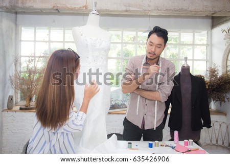 Young asian man designer and woman talking about concept for design woman dress.