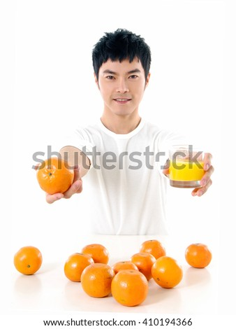 Young Asian man drinking juice with pile of orange