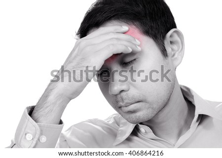 Young Asian man having headache with hand on his forehead - monochrome effect with red spot on pain area - stock photo