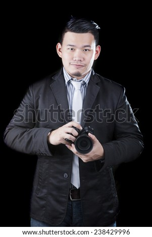 young asian man holding dslr camera take a photography by low key ,low light white dark background technical use for people activities and human occupation career - stock photo