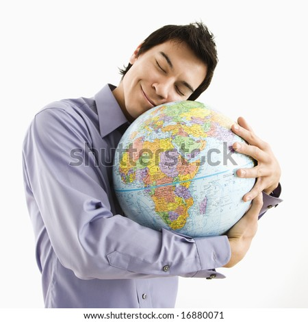 Young Asian man holding globe with happy expression on his face. - stock photo