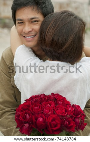 Young Asian man hugging his girlfriend and holding Roses - stock photo