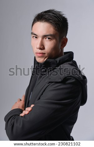 Young asian man in business against gray background