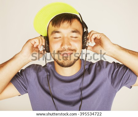 young asian man in hat and headphones listening music on white background