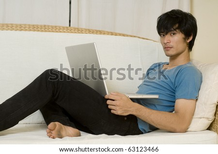 Young Asian man laying on sofa and using computer - stock photo