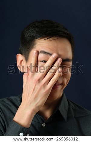 Young Asian man looking at camera through his fingers  - stock photo