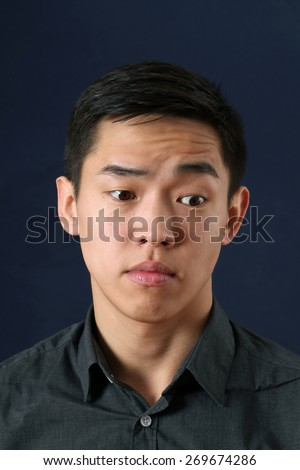Young Asian man looking sideways down - stock photo