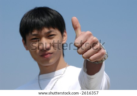 Young Asian man making a thumb up saying OK - hand in focus - stock photo