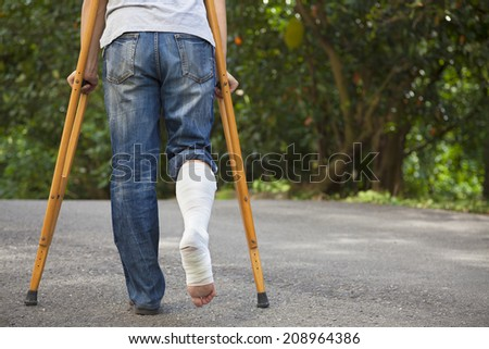 Young asian man on crutches with tree background - stock photo