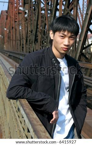 Young Asian man on the railway bridge - stock photo