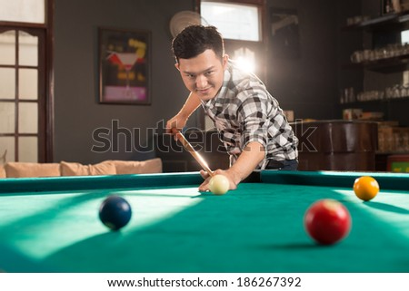 Young Asian man playing pool in the bar - stock photo