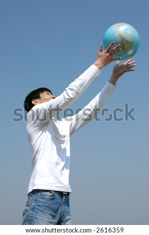 Young Asian man playing with a terrestrial globe - stock photo
