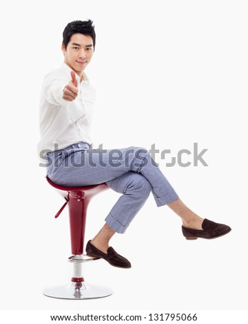 Young asian man showing thumb on the isolated on white background. - stock photo