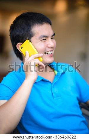 Young Asian man talking on the phone, selective focus on phone. - stock photo