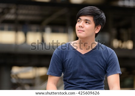 Young asian man thinking outdoors