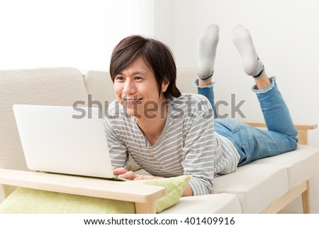 young asian man using laptop computer