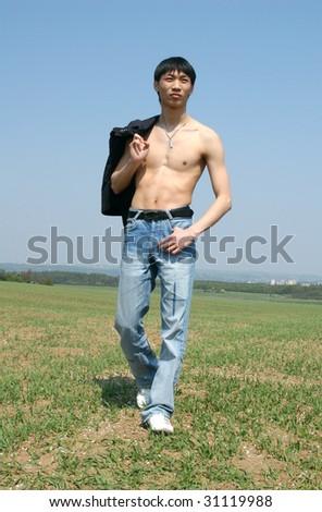 Young Asian man walking through the meadow - stock photo