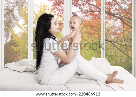Young asian mother playing with her baby on bedroom at home in autumn - stock photo