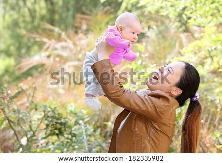 Young Asian Mother Playing with her Young Baby in the Park - stock photo
