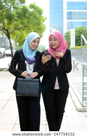 Young asian muslim businesswomen in head scarf looking handphone while walking