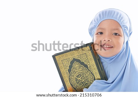 Young Asian Muslim girl in blue hijab hold a Al Quran. - stock photo