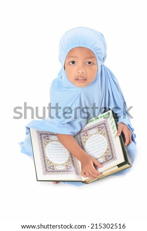 Young Asian Muslim girl in blue hijab reading Al Quran - stock photo
